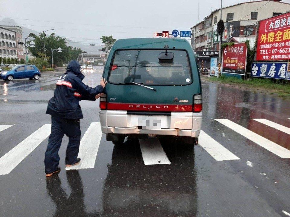 豪大雨車輛拋錨 旗熱心警雨中推車。(記者劉明吉翻攝)