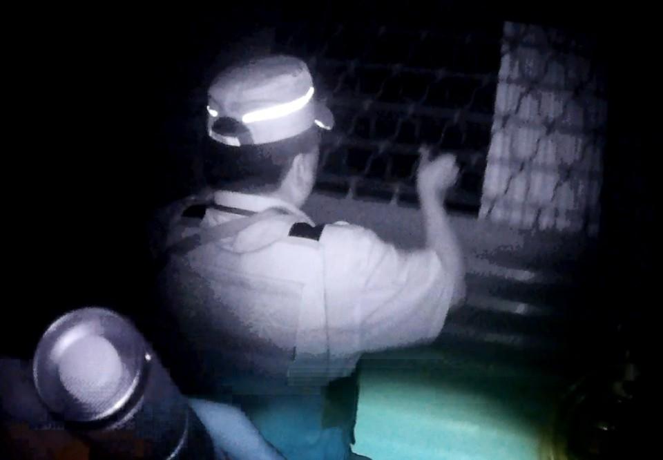 巡佐林中川徒手拉開鐵門協助婦人脫困。(記者劉明吉翻攝)
