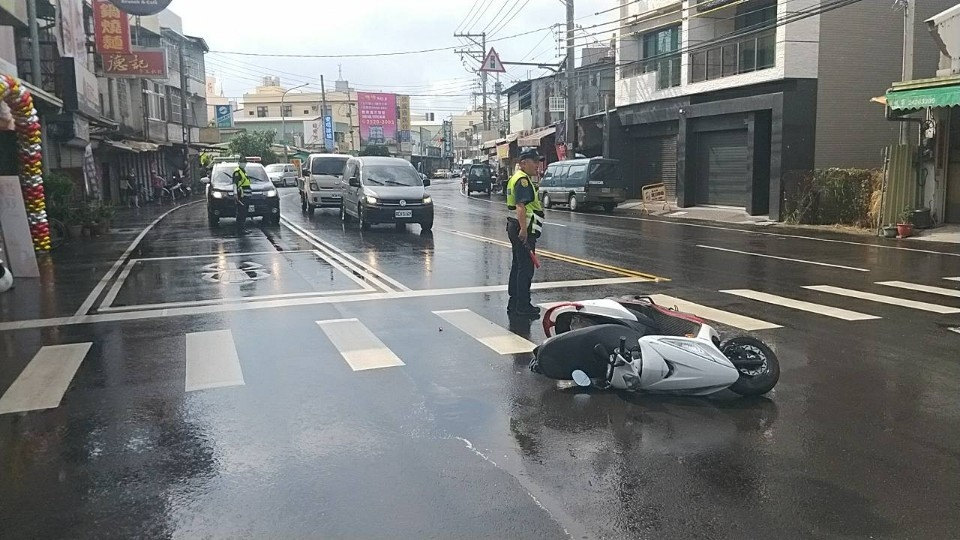 雨天騎士交通事故 警方幫忙交整成最美風景。(記者張越安翻攝)