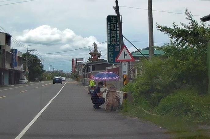 烈日當空老婦頭暈跌倒 旗警撐傘遮陽協助送醫。(記者劉明吉翻攝)